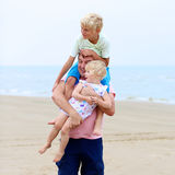 Ojcuje z dzieciakami ma zabawę na plaży Obrazy Royalty Free