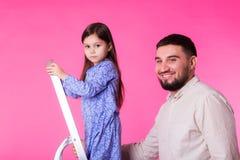Ojcuje z jego dziecko córką ono uśmiecha się nad różowym tłem zdjęcia stock