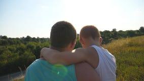 Ojcuje z jego małym synem wydaje czas wpólnie plenerowego przy łąką Tata i dziecka obsiadanie przy zieloną trawą na zbiory wideo