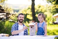 Ojcuje z małą córką outside, malujący drewnianego birdhouse Fotografia Royalty Free