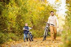 Ojcuje z małym syna kolarstwem w jesień parku fotografia stock