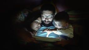 Ojcuje z małymi dziećmi surfuje na pastylka komputerze przed spać zdjęcie wideo