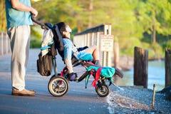 Ojcuje z niepełnosprawnym synem w wózku inwalidzkim przy parkiem, cieszy się zmierzch obrazy royalty free