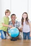Ojcuje z syna i córki rekonesansową mapą na kuli ziemskiej Obraz Royalty Free