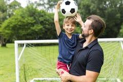 Ojcuje z synem bawić się futbol na futbolowej smole Fotografia Stock