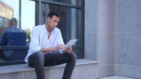 Ojeada al aire libre en la tableta, hombre hermoso negro joven