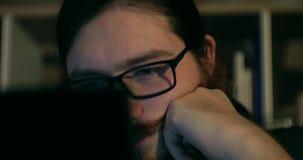 Ojeada de charla del hombre barbudo en de última hora - tiro ascendente cercano con la reflexión de los vidrios de la exhibición almacen de video