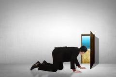 Ojeada de la toma del hombre de negocios en pequeña puerta a través de la playa Imagenes de archivo