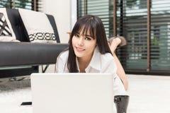 Ojeada en línea de la muchacha feliz en el ordenador portátil Fotos de archivo libres de regalías