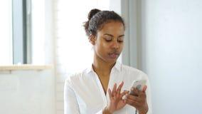 Ojeada Smartphone, mujer negra del envío de mensajes de texto almacen de video