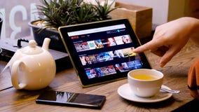 Ojeada a través de la biblioteca de Netflix de películas y de demostraciones almacen de video