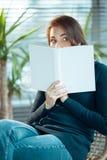 Ojeadas de la muchacha de detrás un libro Fotografía de archivo
