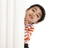 Ojeadas sonrientes del niño de detrás una columna fotos de archivo libres de regalías