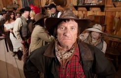 Ojämn Cowboy i en salong Fotografering för Bildbyråer