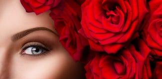 Ojo azul de la mujer hermosa con las rosas rojas Imágenes de archivo libres de regalías