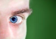 Ojo azul humano hermoso, macro, cierre encima de la mirada lateral en el CCB verde Imágenes de archivo libres de regalías