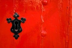 Ojo de la cerradura negro en puerta de madera roja Fotografía de archivo libre de regalías