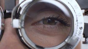 Ojo de la mujer con el primer de ensayo óptico del marco, examen de la agudeza visual, la óptica almacen de video