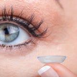 Ojo de la mujer con la aplicación de la lente de contacto Imagenes de archivo