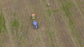 Ojo del p?jaro del hombre en el trabajo sobre el tractor con la prensa del heno almacen de video