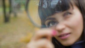 Ojo del ` s de la mujer que mira a través de una lupa almacen de metraje de vídeo