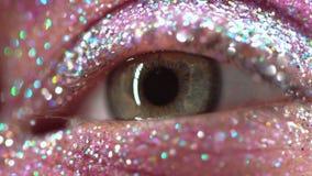 Ojo femenino verde macro con el sombreador de ojos del brillo, chispas coloridas, cristales Fondo de la belleza, maquillaje del e metrajes