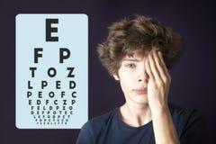 Ojo masculino joven de la visión y de la cubierta del ojo de la prueba con la mano b imagenes de archivo