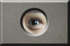 Ojo que mira a través del agujero en ladrillo Imagenes de archivo