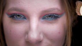 Ojo-retrato del modelo rubio con el maquillaje colorido alegre que se come con los ojos la cámara en fondo borroso de las luces almacen de metraje de vídeo
