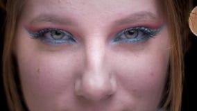 Ojo-retrato del modelo rubio con el maquillaje colorido que aumenta sus cejas juguetónamente en fondo borroso de las luces metrajes