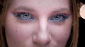 Ojo-retrato del modelo rubio con el maquillaje colorido que aumenta sus cejas y que se come con los ojos la cámara en luces borro metrajes