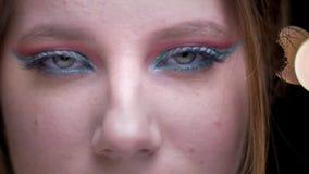 Ojo-retrato del modelo rubio con el maquillaje colorido que mira atento en cámara en fondo borroso de las luces almacen de metraje de vídeo