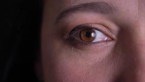 Ojo-retrato del primer de la mujer de mediana edad que mira risueñamente en cámara en fondo negro almacen de video