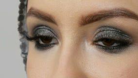 Ojos ahumados del maquillaje hermoso de un modelo profesional de la muchacha Los ojos marrones de las mujeres con las pestañas la almacen de video