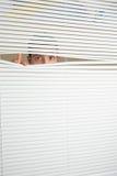 Ojos asombrosos del varón que espían a través de persianas de rodillo Imagenes de archivo