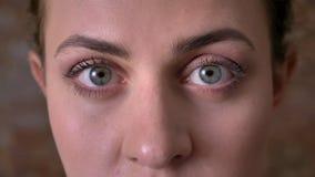 Ojos azules del primer hermoso de la mujer joven caucásica que está mirando derecho la cámara con confianza almacen de metraje de vídeo