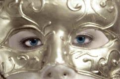 Ojos azules detrás de la máscara imagenes de archivo