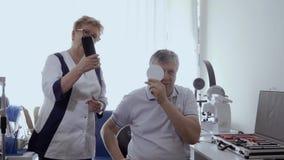 Ojos de examen del oculista del hombre mayor en clínica almacen de metraje de vídeo