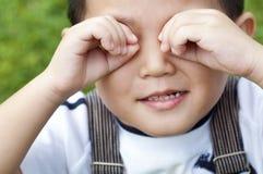 Ojos de la cubierta del muchacho imagen de archivo
