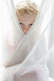 Ojos de la pequeña muchacha rubia ocultada por la cortina Imagenes de archivo