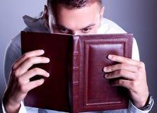 Ojos del hombre sorprendido sobre el libro marrón imagenes de archivo