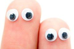 Ojos del meneo pegados en los dedos Imagen de archivo