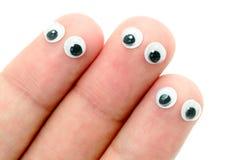 Ojos del meneo pegados en los dedos Imagenes de archivo