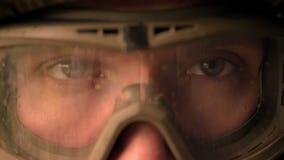 Ojos del primer del soldado caucásico en casco y del camuflaje que mira derecho la cámara, tranquilamente, la mirada persistente, almacen de video