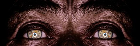 Ojos del viejo hombre en obscuridad Fotos de archivo