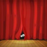 Ojos detrás de las cortinas rojas en la etapa de madera Fotos de archivo libres de regalías