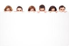 Ojos divertidos que miran a escondidas detrás de whiteboard Fotografía de archivo