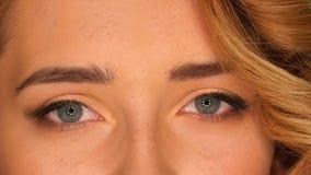 Ojos marrones hermosos de la mujer rubia joven, cierre almacen de video