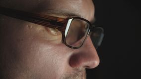 Ojos masculinos del empresario en las lentes que miran la pantalla del ordenador portátil y que trabajan tarde en la noche Mirada almacen de metraje de vídeo