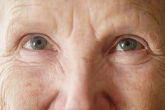 Ojos mayores de la abuela de la mujer que miran al cierre de la cámara encima del retrato foto de archivo libre de regalías